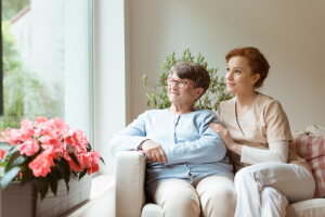 senior woman and her caregiver sitting