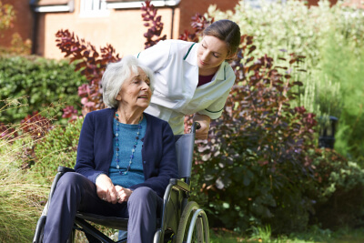 senior woman sitting in wheelchair with caregiver