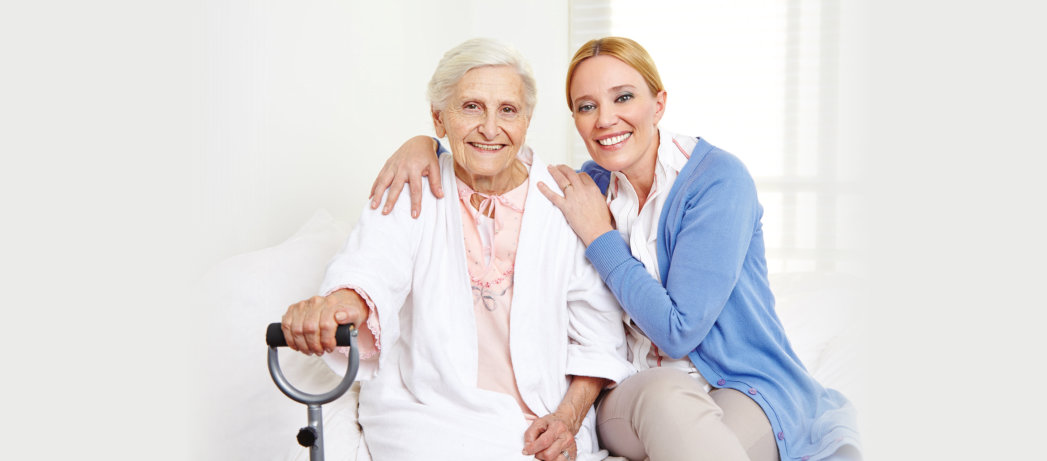 caregiver with a senior woman smiling