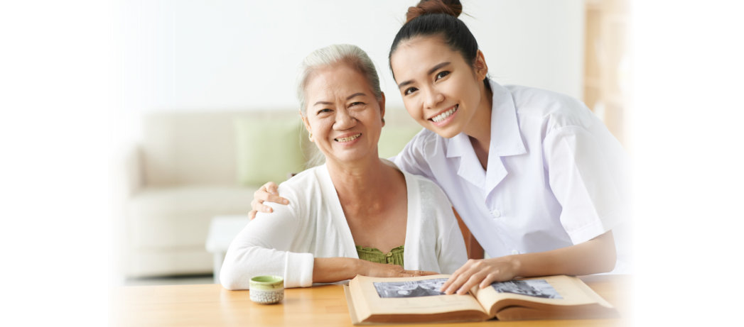 caregiver helping the senior woman in reading the book