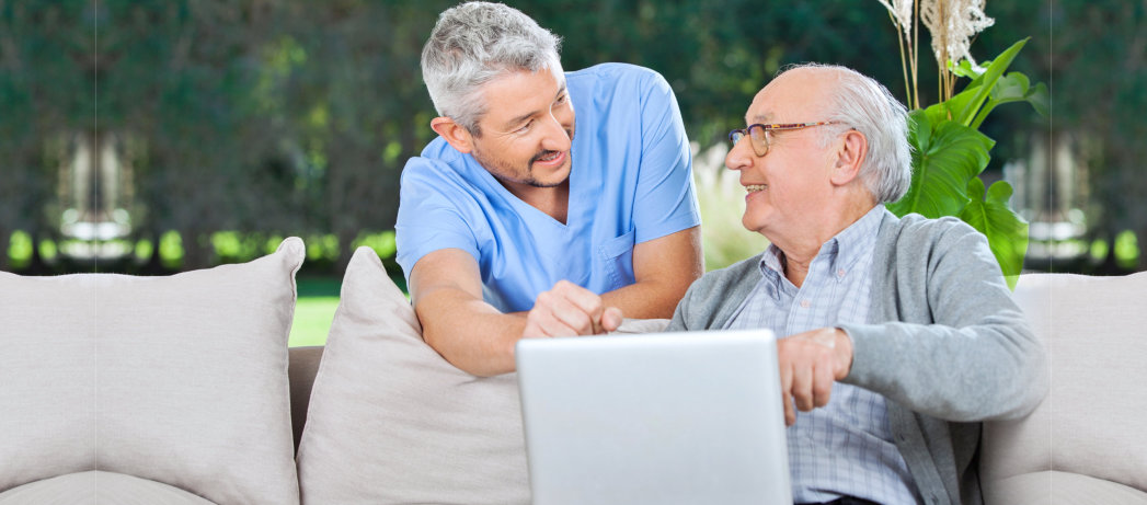 caregiver assisting the old man in using laptop