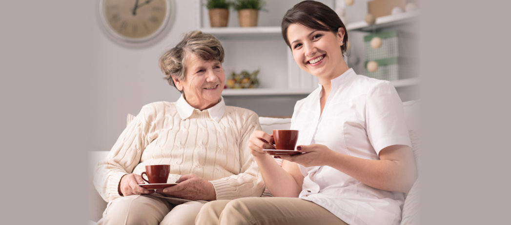 caregiver and senior woman having a coffee