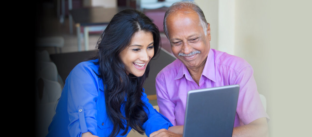 caregiver assisting the old man in using the laptop